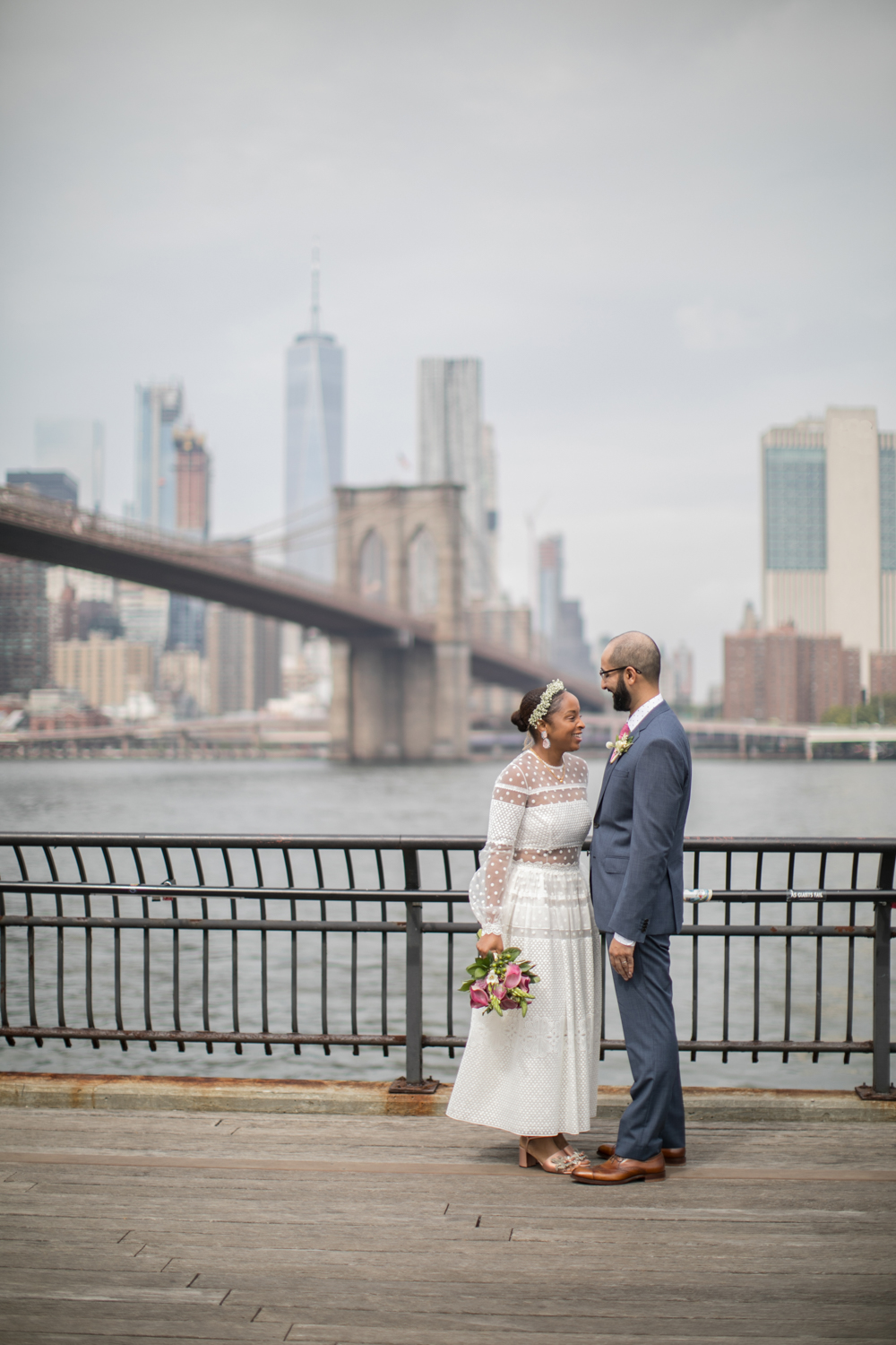 A bride and groom pose for a portrait in Brooklyn Bridge Park.