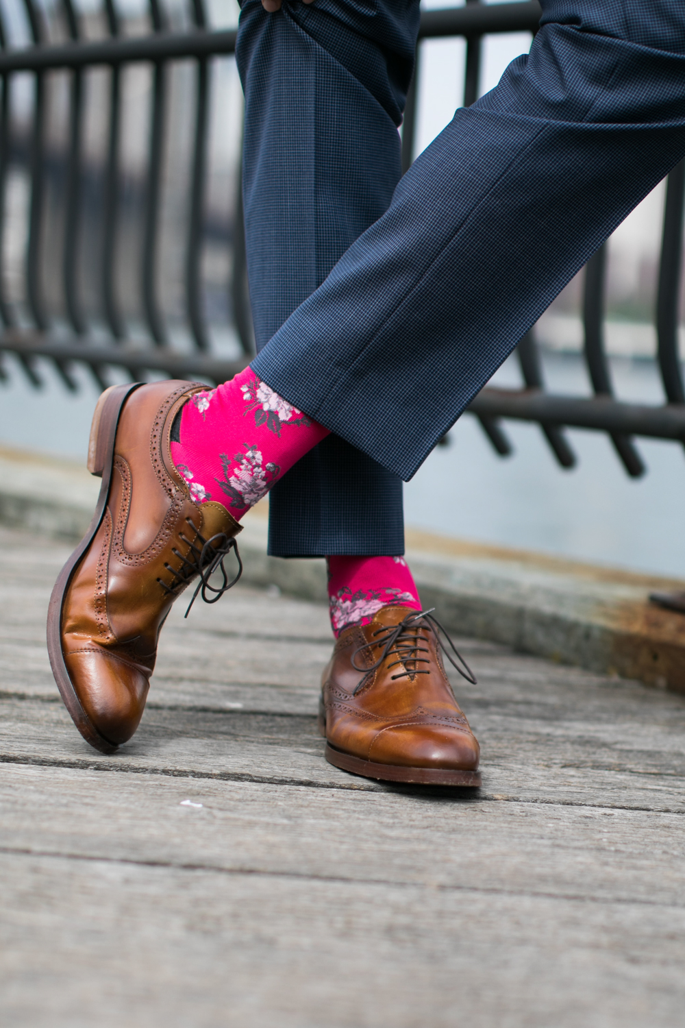 Close up of a groom's brown shoes and flowered socks in Brooklyn Bridge Park.