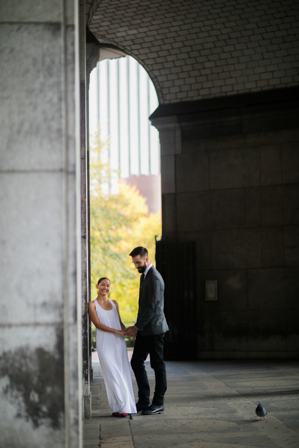 A bride and groom smile while holding hands in the park.
