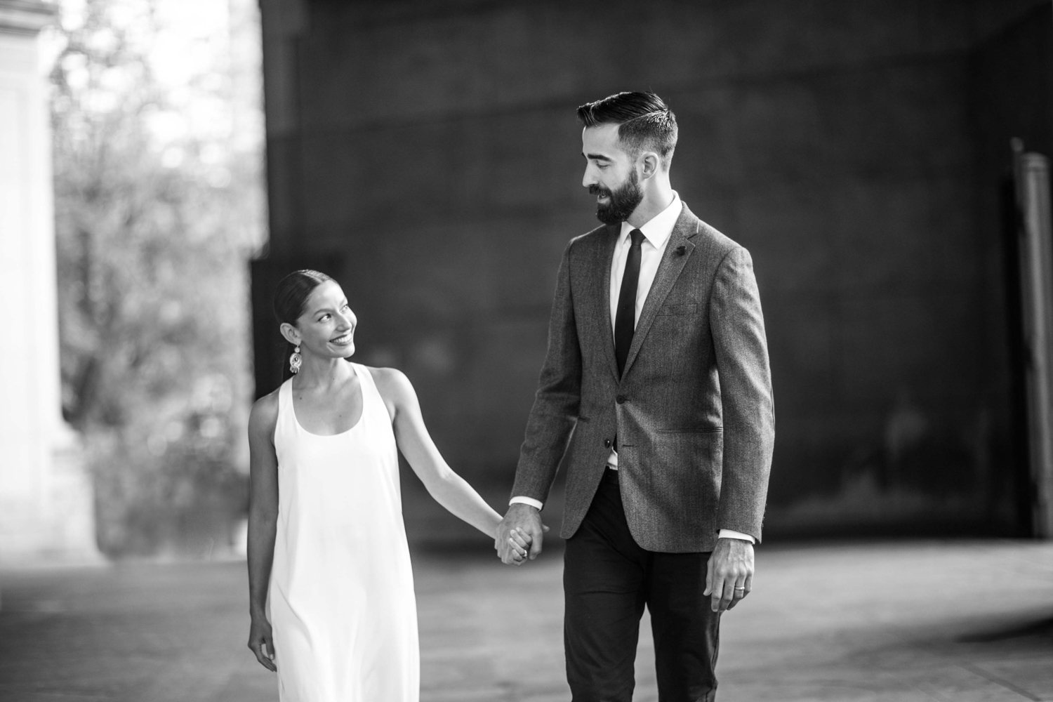 Black and white portrait of newlyweds holding hands after their wedding.