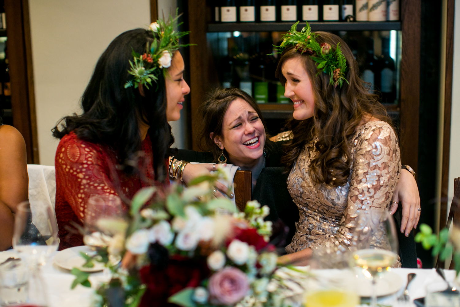 Brides laugh with a friend at their lunch wedding reception at Maialino in New York City.