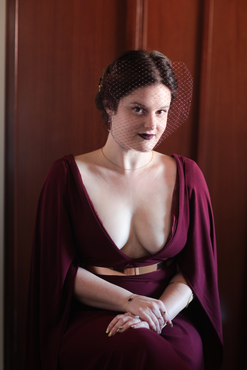Portrait of the bride in a caped burgundry wedding dress.