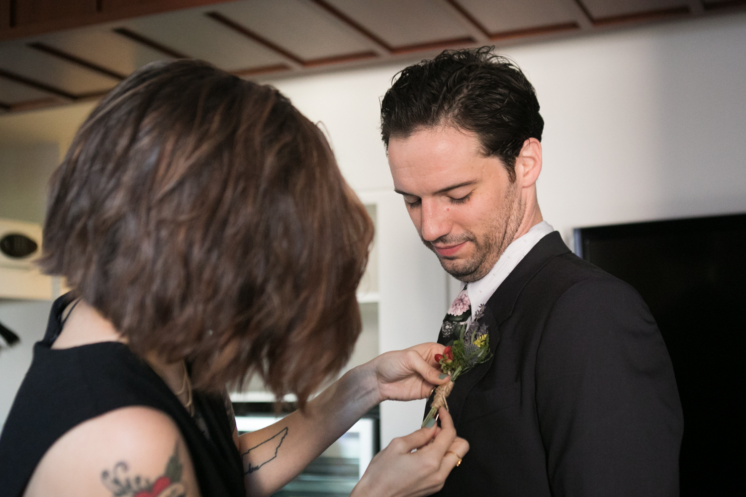 Pinning the boutineere on the groom.