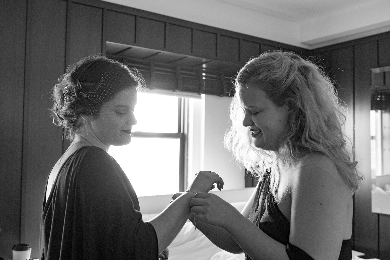 Bridesmaid helps the bride put on a bracelet.