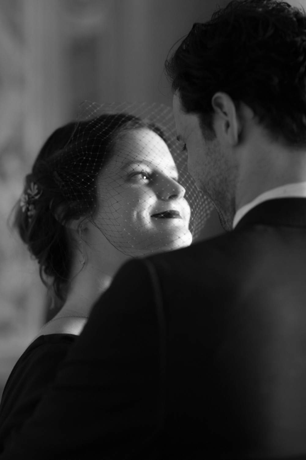 Black and white portrait of a bride in a birdcage veil looking at her husband.