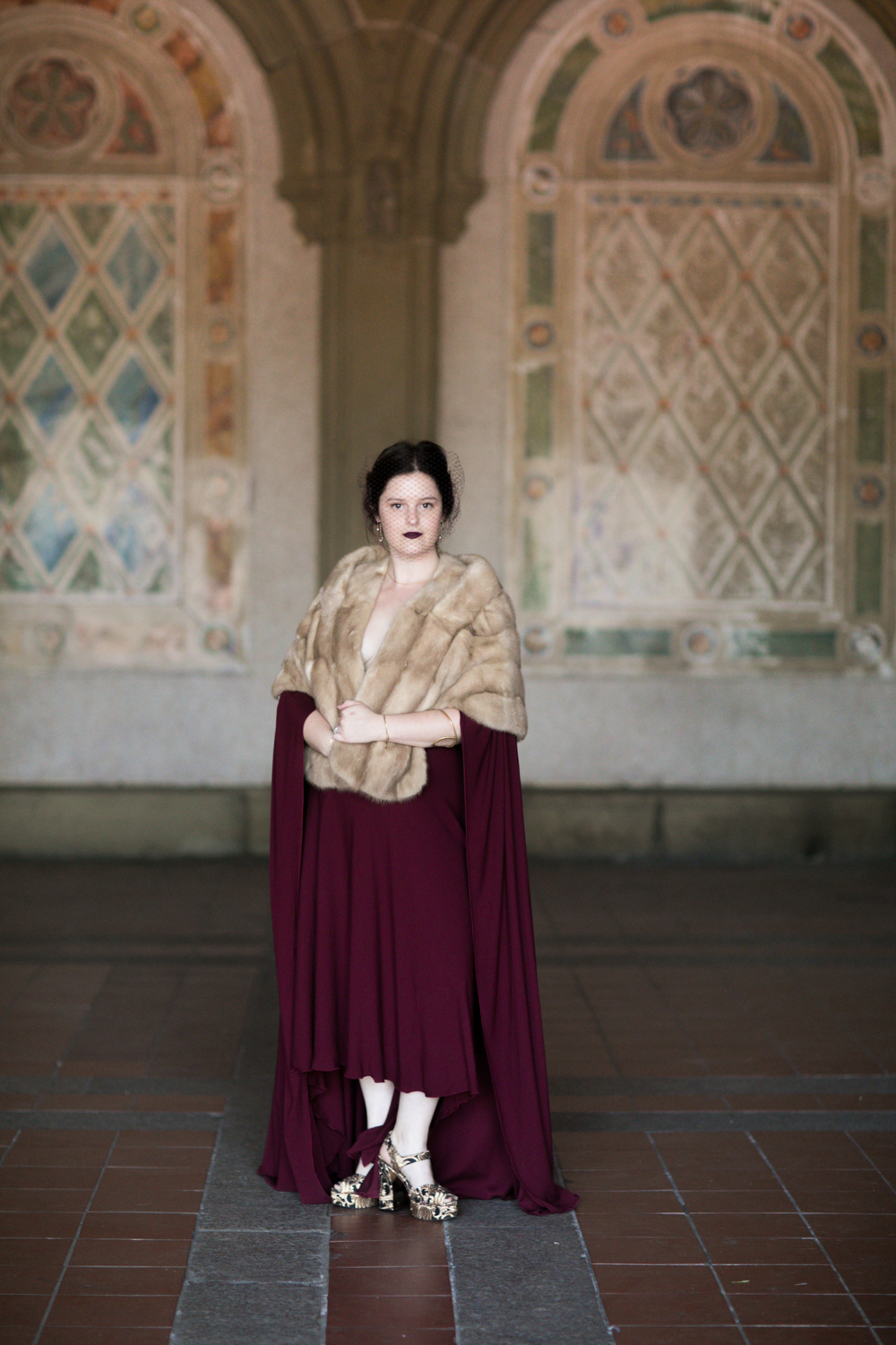 Portrait of the bride in a caped burgundy dress and an antique fur.