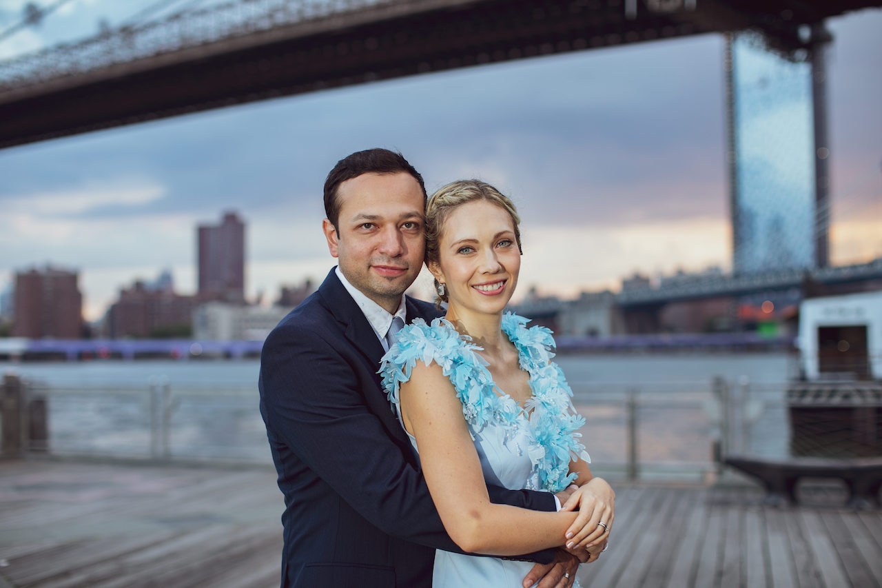 A couple poses in front of the Brooklyn Bridge at Sunrise | Brooklyn Bridge Anniversary Session | Brooklyn Bridge Wedding Photos | Early morning Brooklyn Bridge Engagement Photos