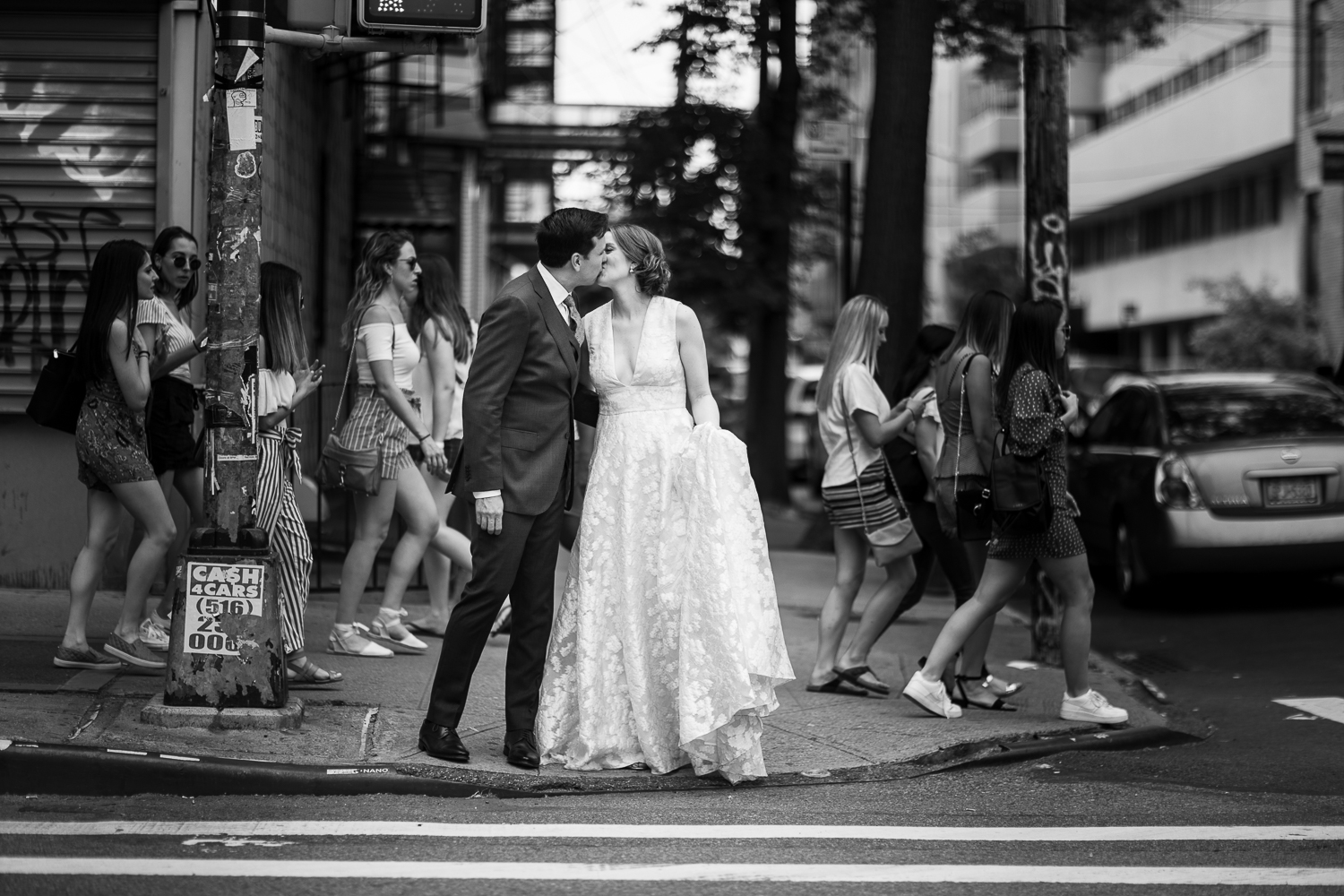 black and white image of the bride and groom kissing as the world goes by