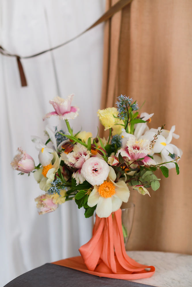 White, pink, and yellow wedding floral arrangement with a coral pink ribbon by FLWR Studio. - NoMad Hotel Wedding in New York City
