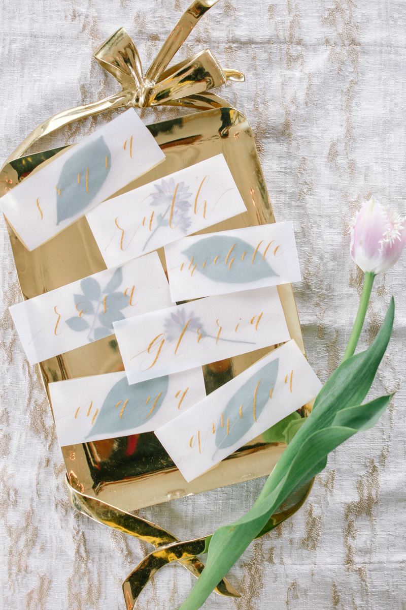 Gold embossed seating cards on a gold tray - Nancy Moy Calligraphy - NoMad Hotel Wedding in New York City