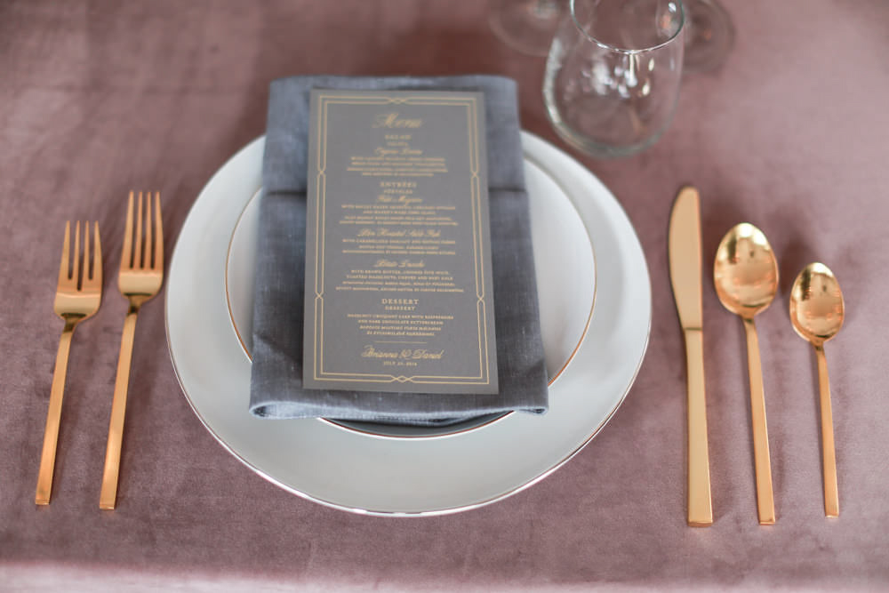 Manhattan wedding -Wedding place setting with a pink tablecloth, gold silverware, a gray napkin, and a gray and gold embossed menu designed by Christa Alexandra Designs - NoMad Hotel Wedding in New York City