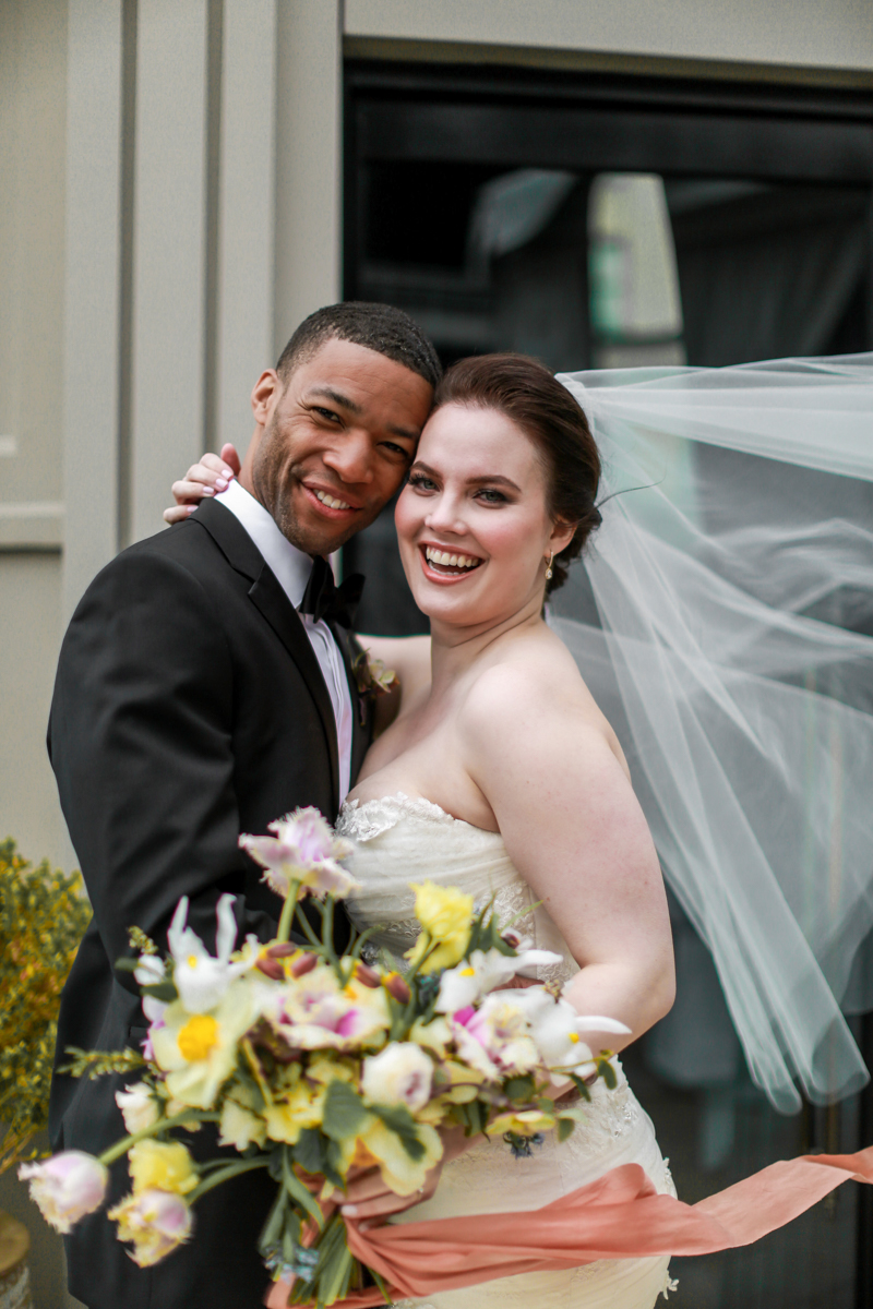 NoMad Hotel Rooftop Wedding in New York City - The bride and groom pose for rooftop portraits and the bride's Jaclyn Jordan wedding veil blows in the wind.