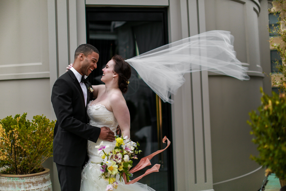 NoMad Hotel Rooftop Wedding in New York City - The bride and groom pose for windswept rooftop wedding portraits and the bride's Jaclyn Jordan wedding veil blows in the wind.