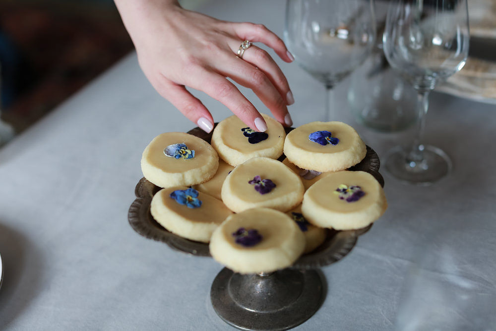 The bride wearing a Bario Neal wedding ring reaches for pressed flower wedding cookies | lNoMad Hotel Wedding in New York City