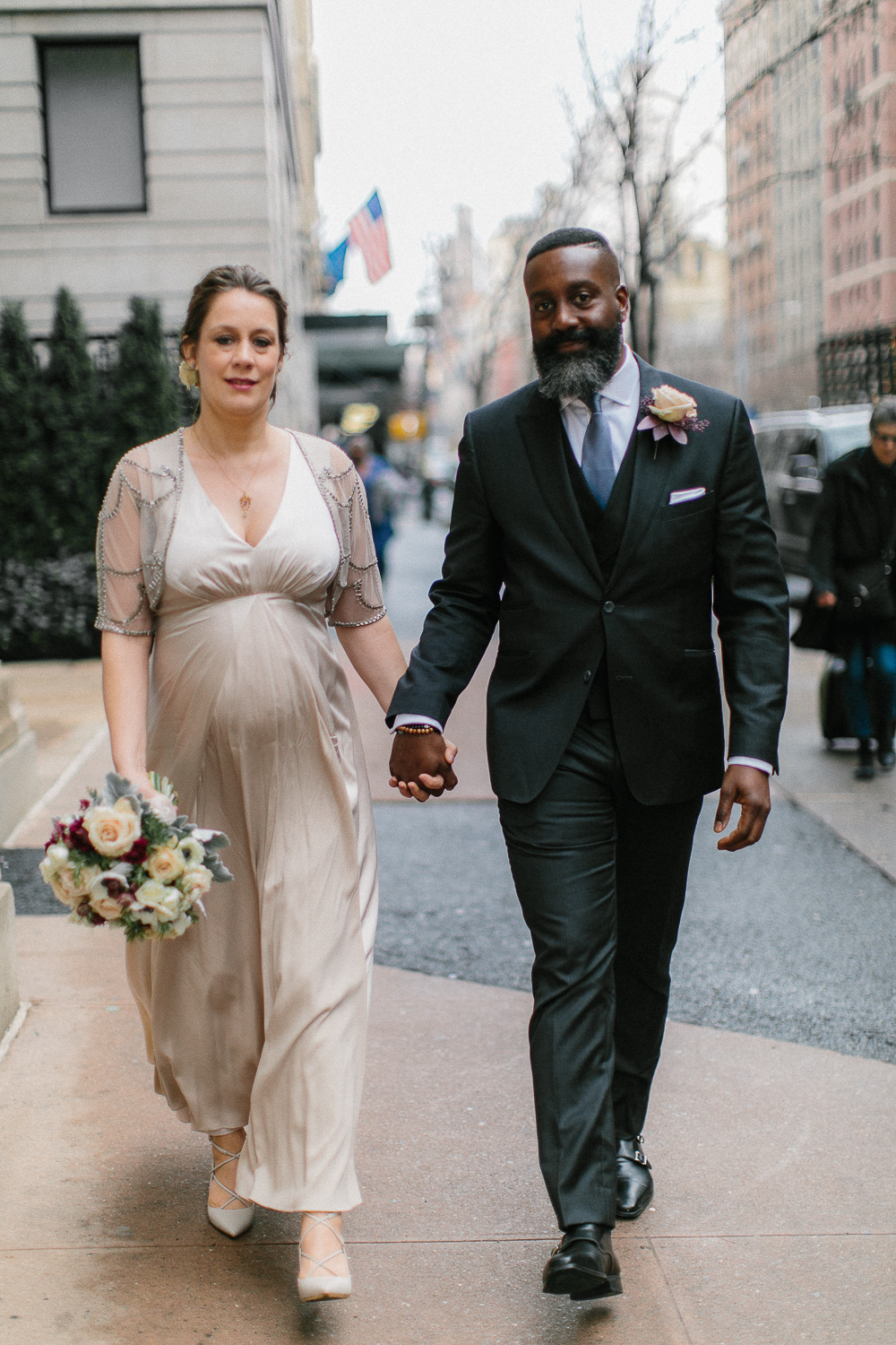 The bride and groom walk down the street outside the Upper West Side Wedding Venue. | Upper West Side Intimate Wedding | Kate & Sylvester's wedding in Manhattan.