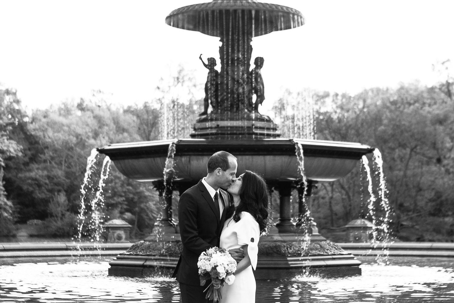 Bride and groom taking wedding photos at Bethesda Fountain in Central Park. | Early Morning Sunrise Central Park Elopement in New York City.