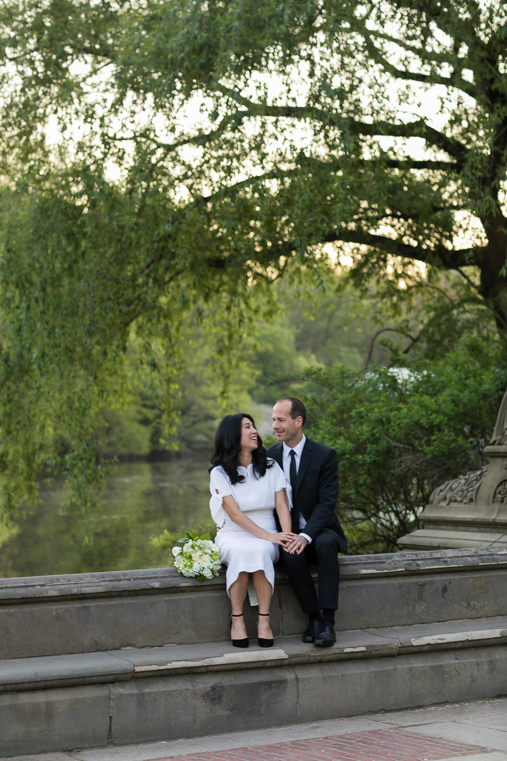 Bride and groom taking wedding photos with weeping willows in Central Park. | Early Morning Sunrise Central Park Elopement in New York City.