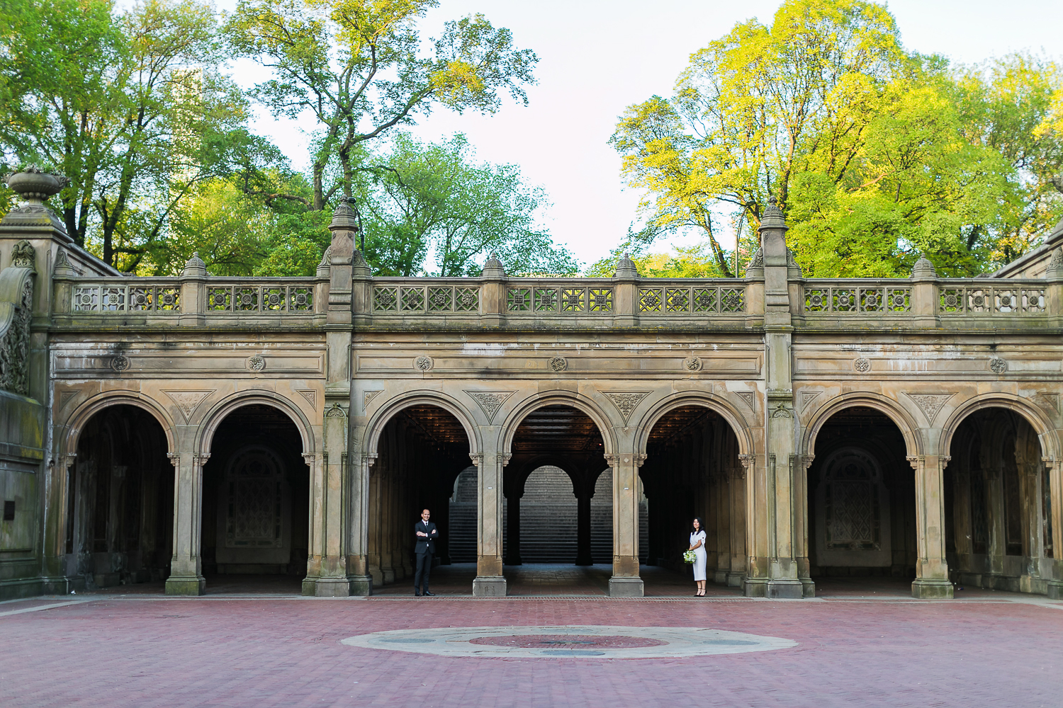 Bride and groom taking wedding photos at Bethesda Terrace in Central Park. | Early Morning Sunrise Central Park Elopement in New York City.