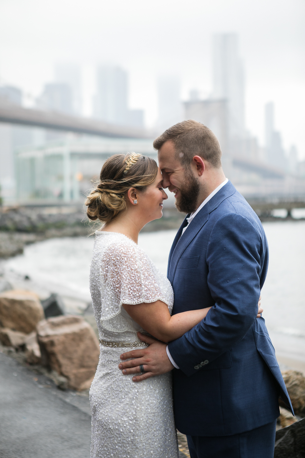 Wedding photos in front of the Brooklyn Bridge. New York Bride in a short wedding dress and groom in a blue suit pose in front of the Brooklyn Bridge. | Intimate Wedding at the Malthouse in Manhattan, New York City.