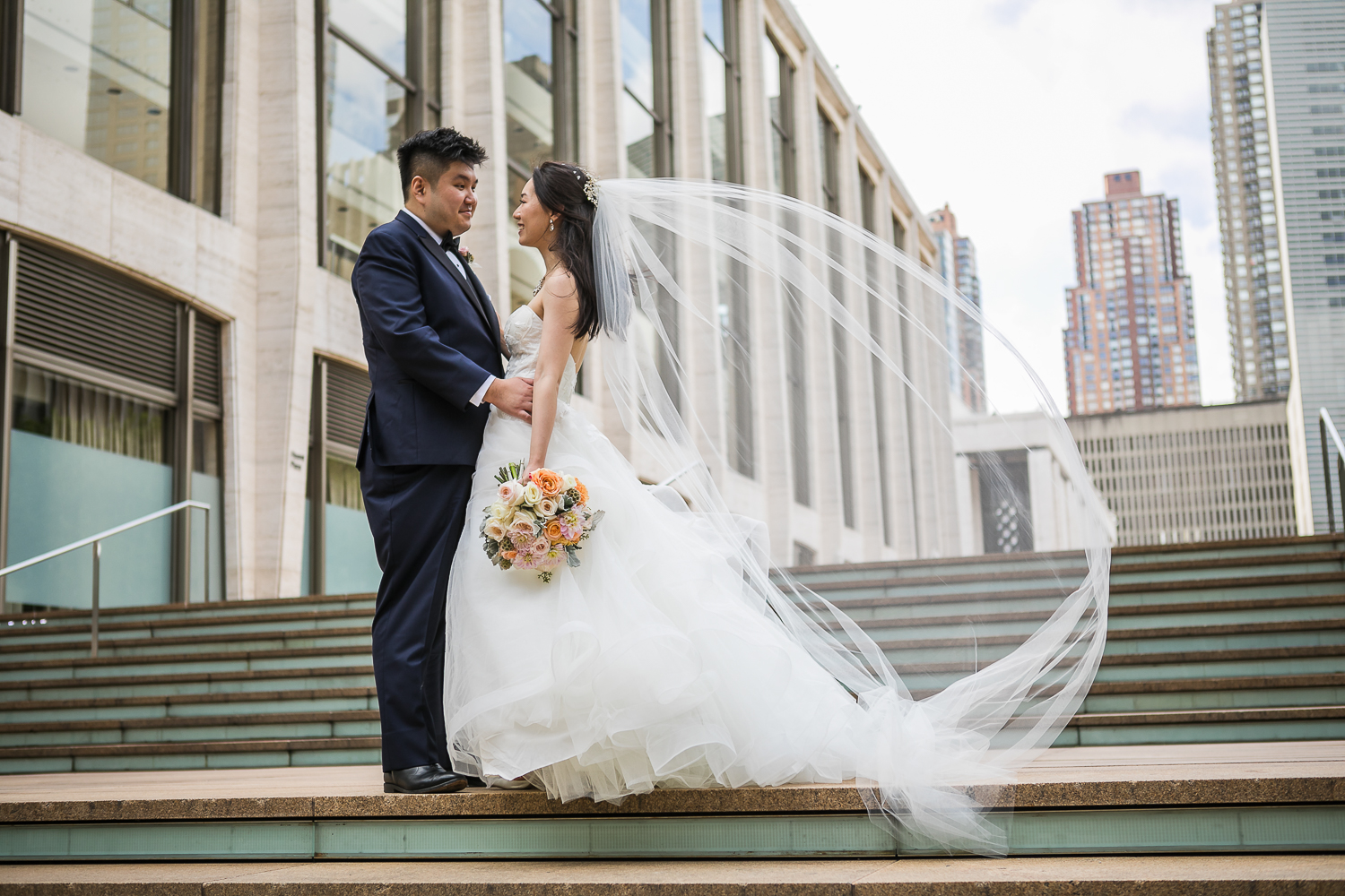 Wind blowing a bride's veil while posing for wedding portraits at Lincoln Center in New York City| Lincoln Center Wedding Photos | Jason and Susanna's Glam NYC Elopement