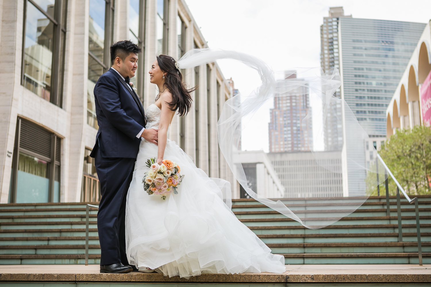 Wind blowing a bride's veil while posing for wedding portraits at Lincoln Center in New York City | Lincoln Center Wedding Photos | Jason and Susanna's Glam NYC Elopement