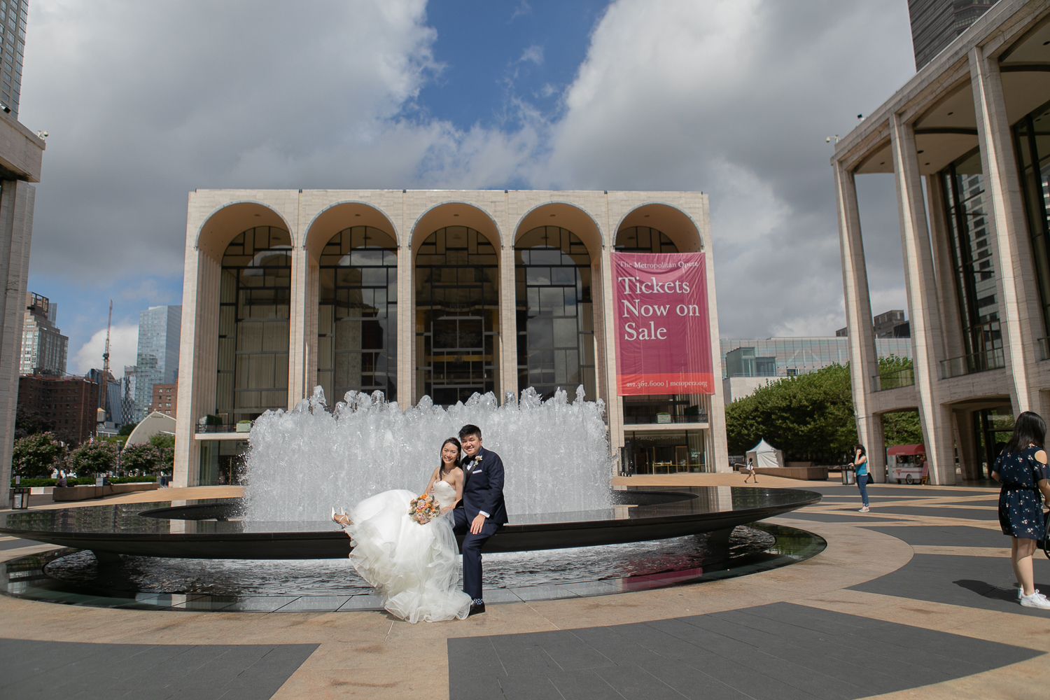 Couple posing for wedding portraits in front of the fountain at Lincoln Center in New York City | Lincoln Center Wedding Photos | Jason and Susanna's Glam NYC Elopement