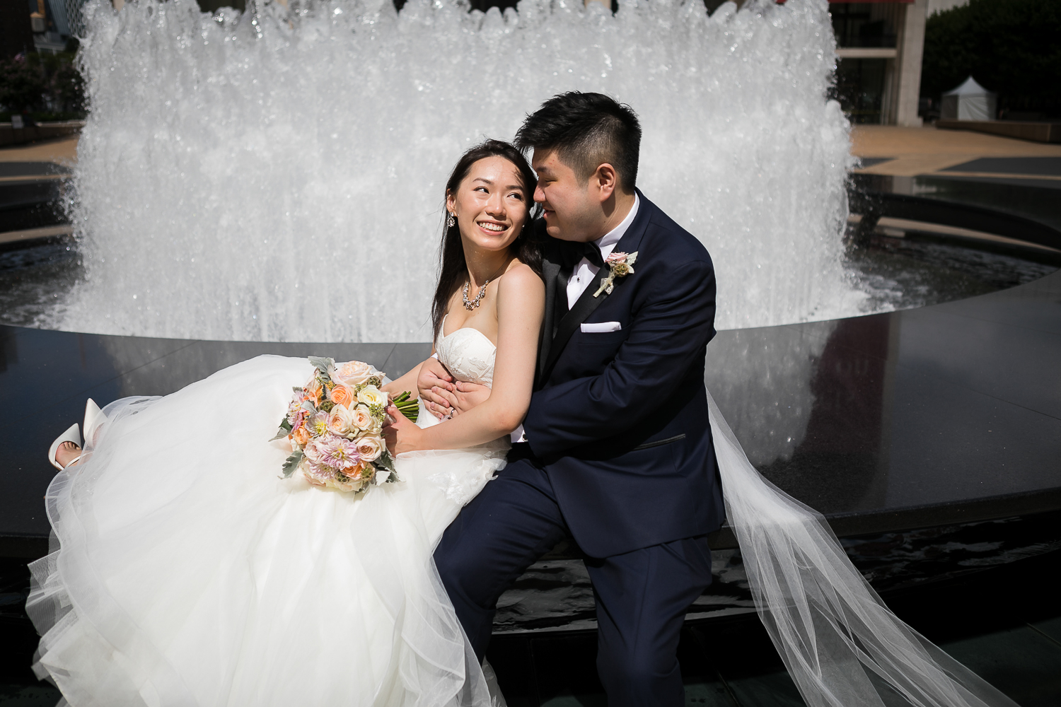 Portrait of a couple posing for wedding portraits in front of the fountain at Lincoln Center in New York City | Lincoln Center Wedding Photos | Jason and Susanna's Glam NYC Elopement