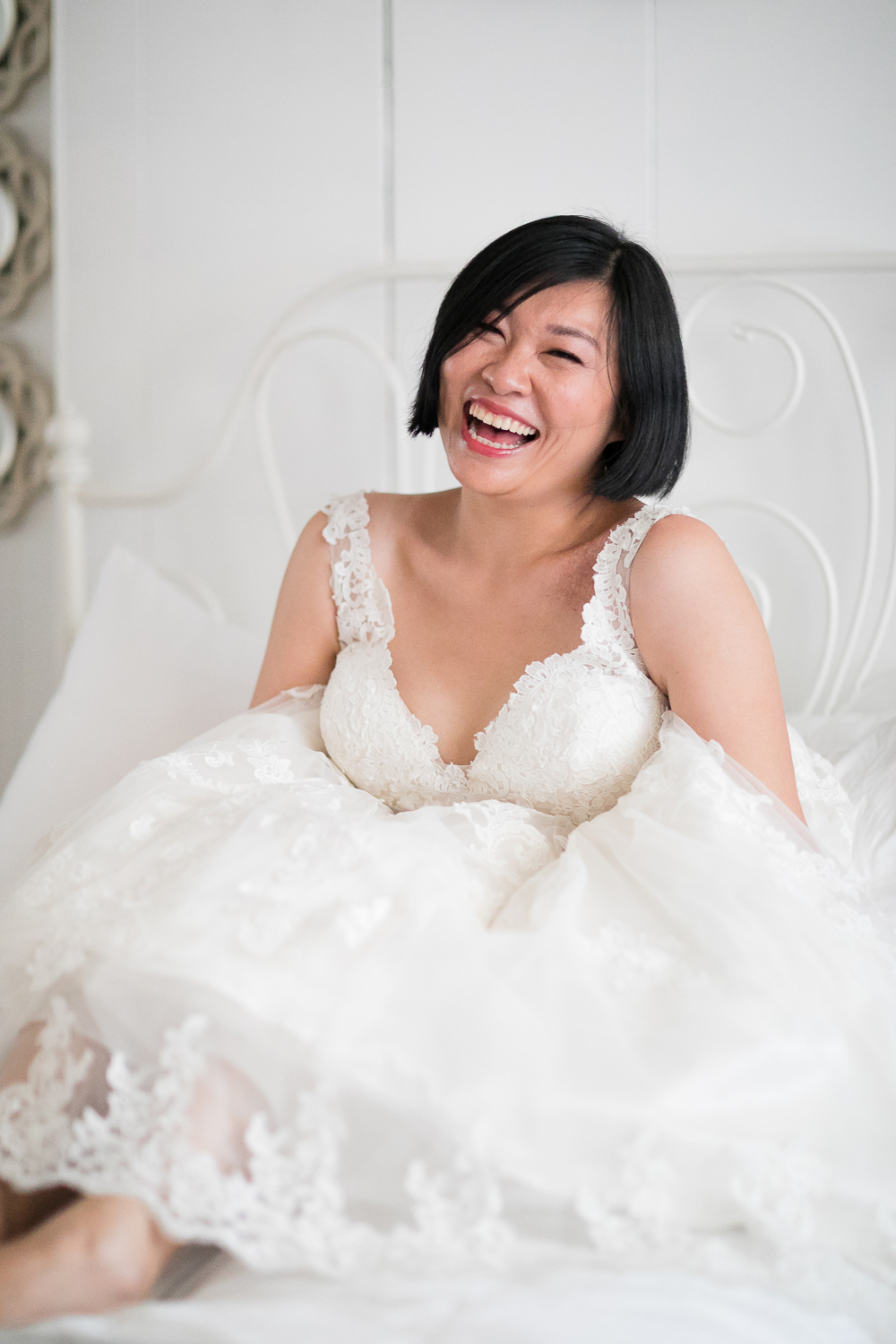 A bride in her wedding gown, laughing while sitting in a poof of a lacy skirt.