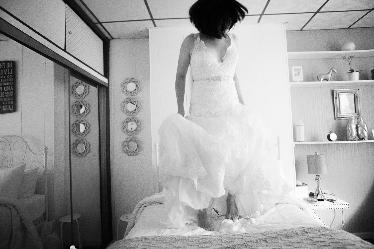 Bride jumping on the bed in her wedding gown.