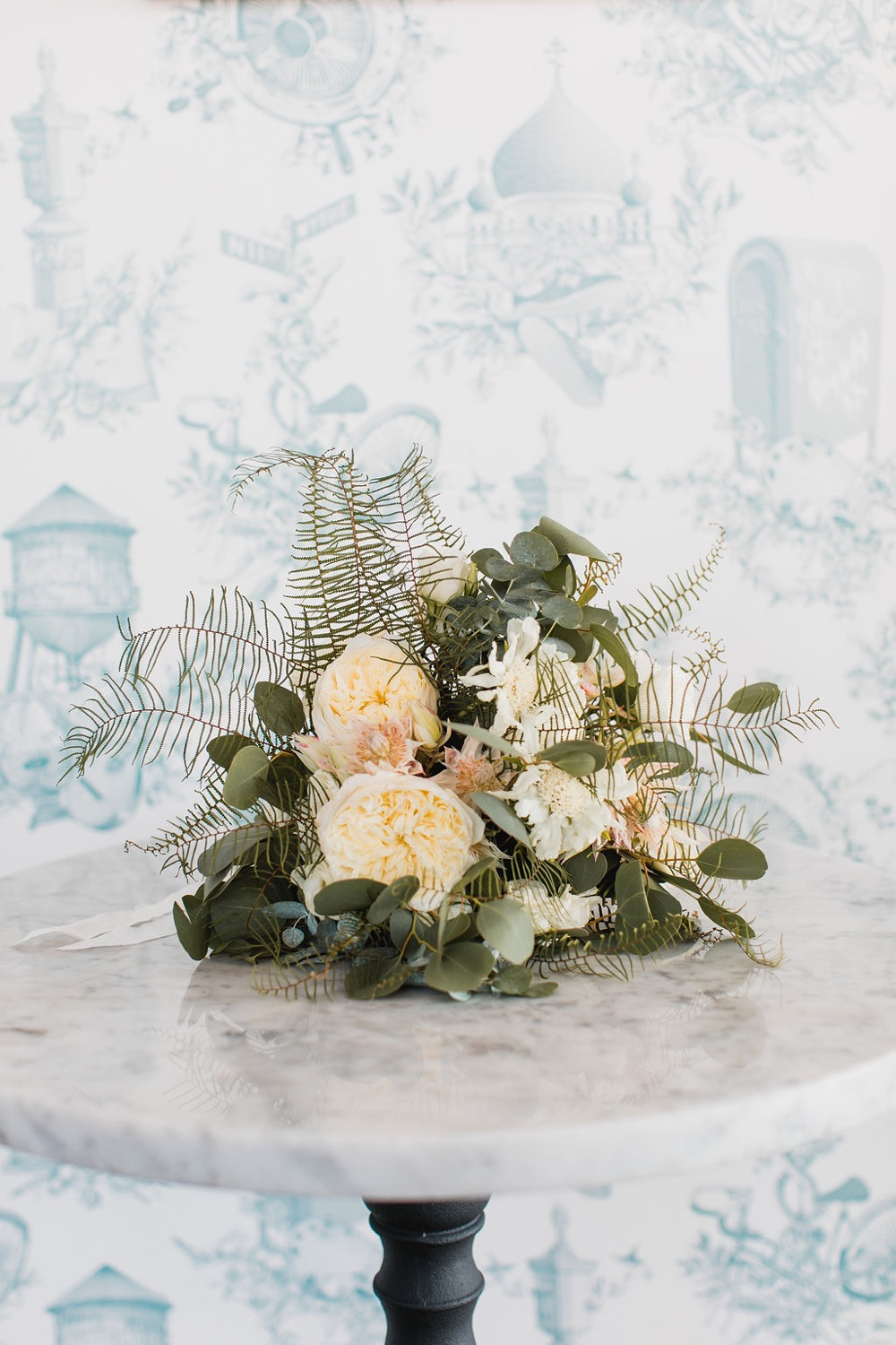 Bride's bouquet made by Mimosa Florals, featuring cream and light peach flowers and lots of greenery. Taken at the Wythe Hotel in Brooklyn.