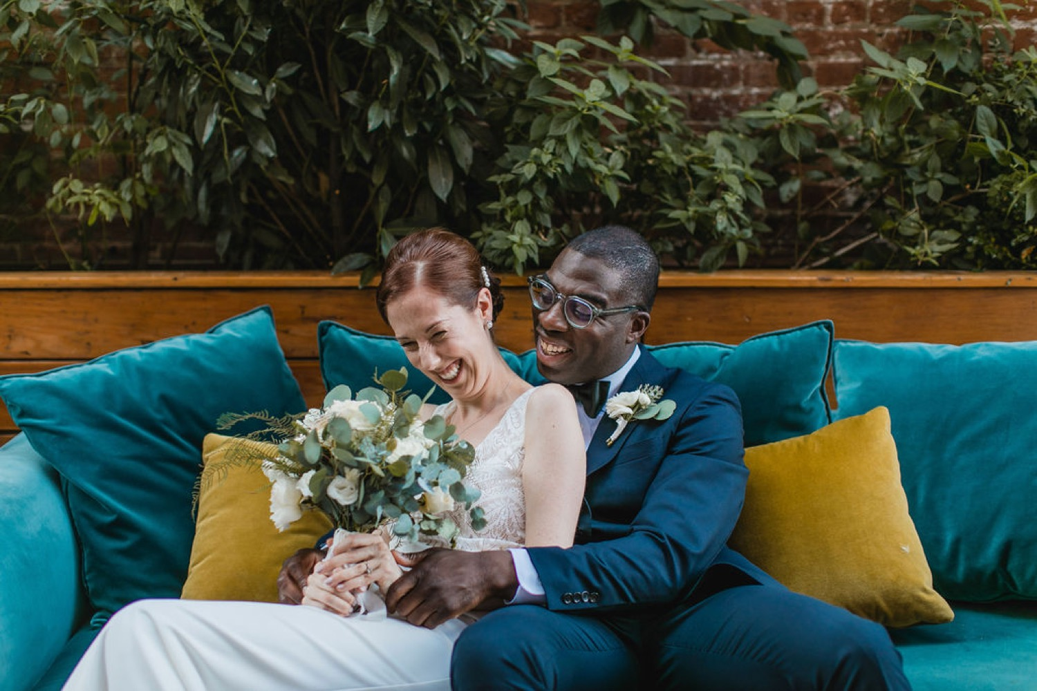 The bride and groom posing on a teal velvet couch at their wedding in NYC.