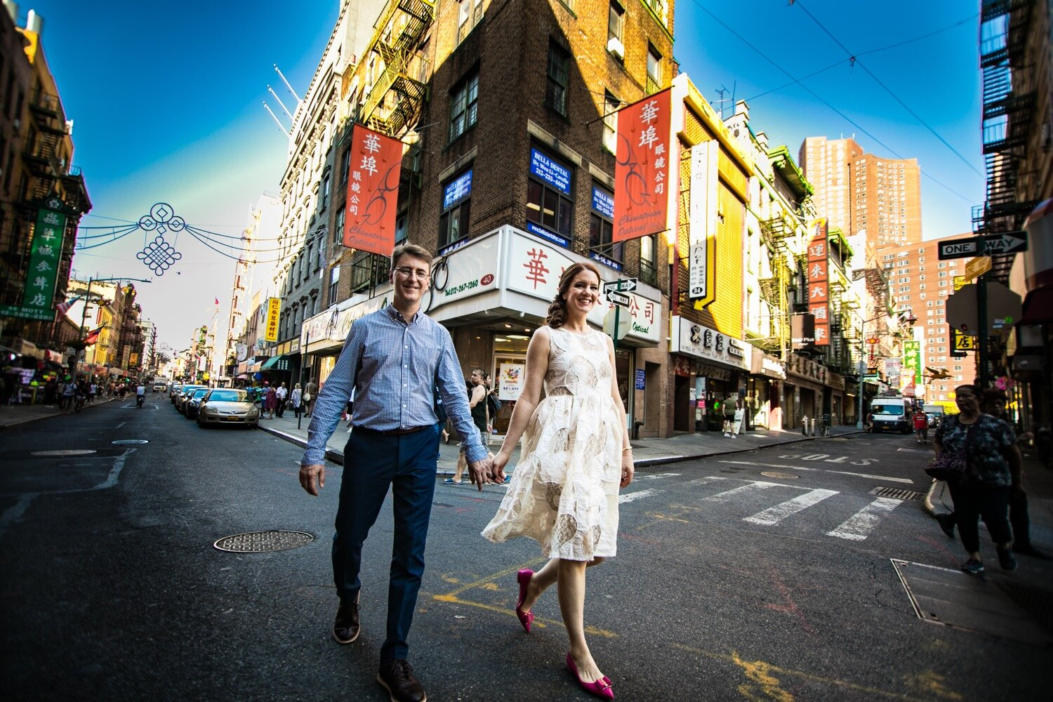 A quirky wedding photo using a wide angle lens, showing the bride and groom in Chinatown, NYC.