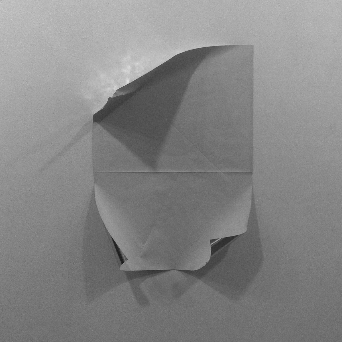 Untitled (from within)  2014, Temporary site specific installation, reflective paper folded and adhered to a wall with an external spotlight. 30 x 30 inches