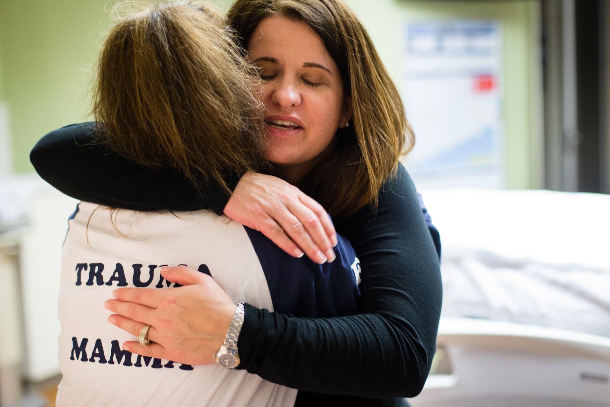 Parker hugs fellow nurse Karyn McComb whose shirt reads,  Trauma Mamma .