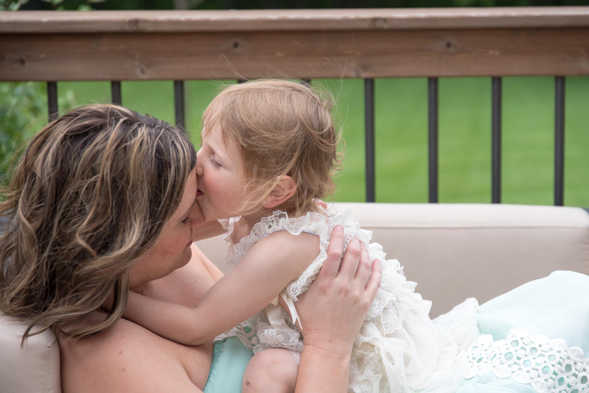 Girl kisses mom's forehead