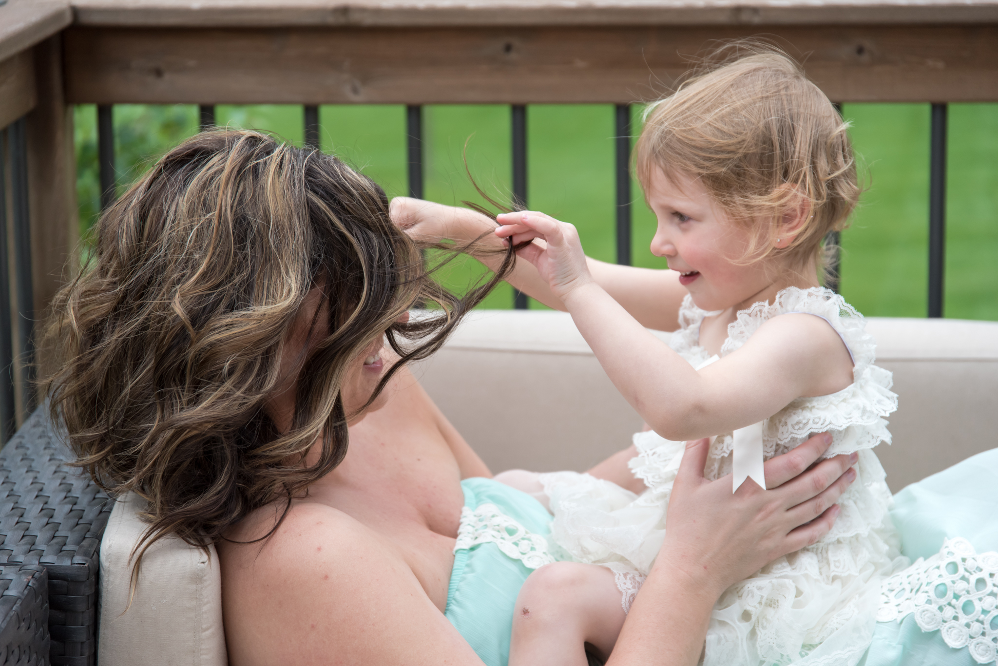 Girl plays with mom's hair
