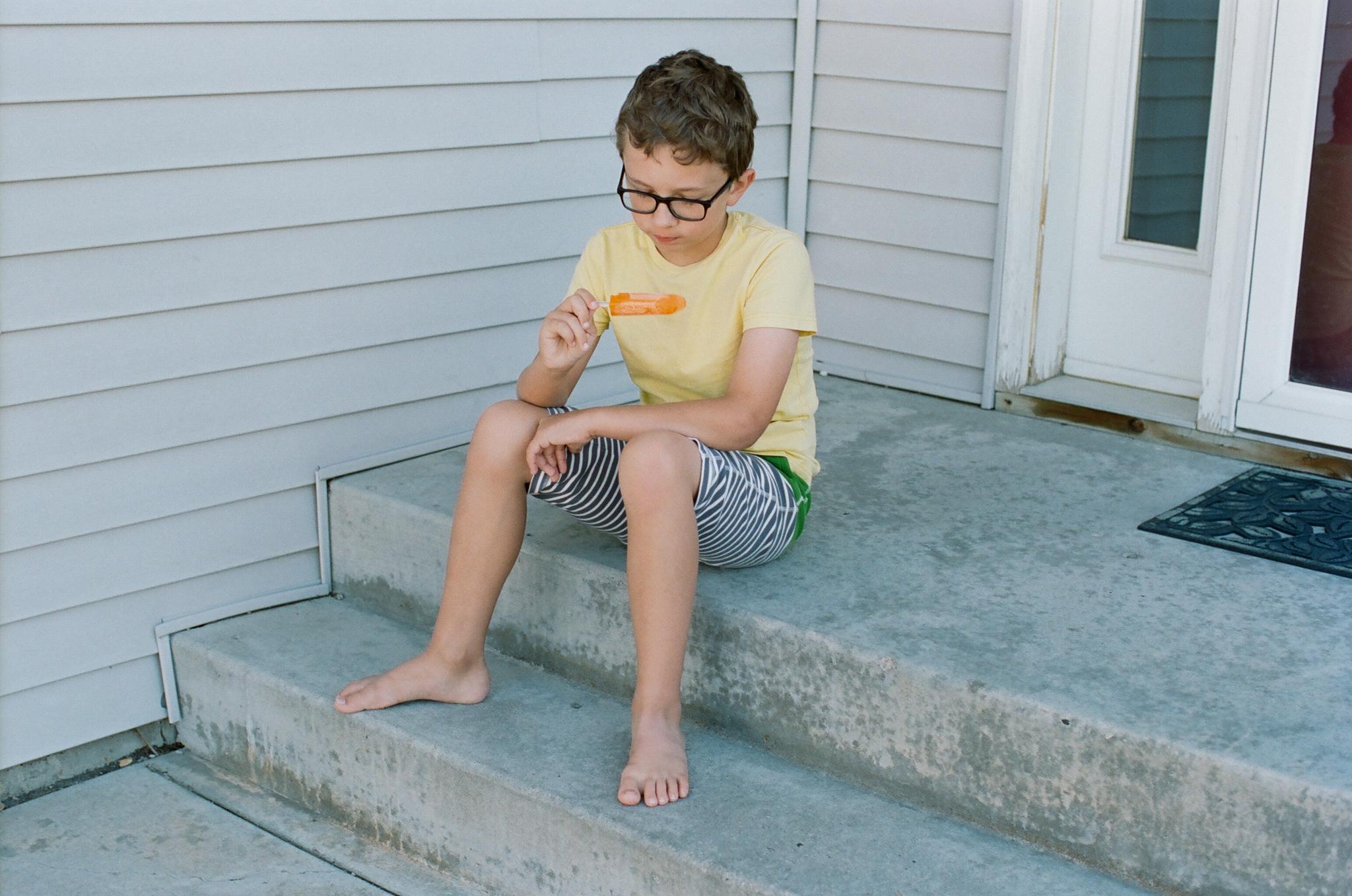 Boy eating orange popsicle