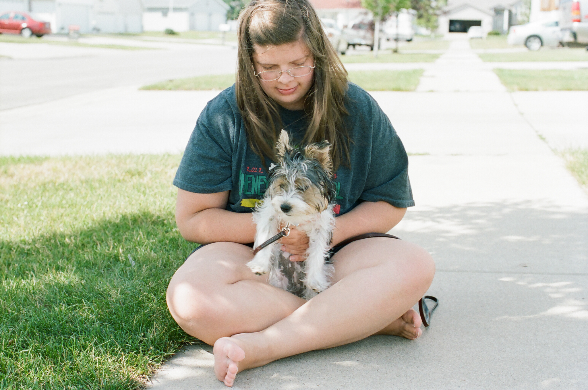 Teen girl and puppy outside.