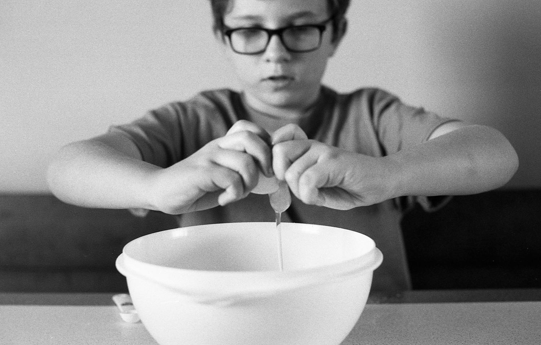 Boy cooking pumpkin mini muffins at home.