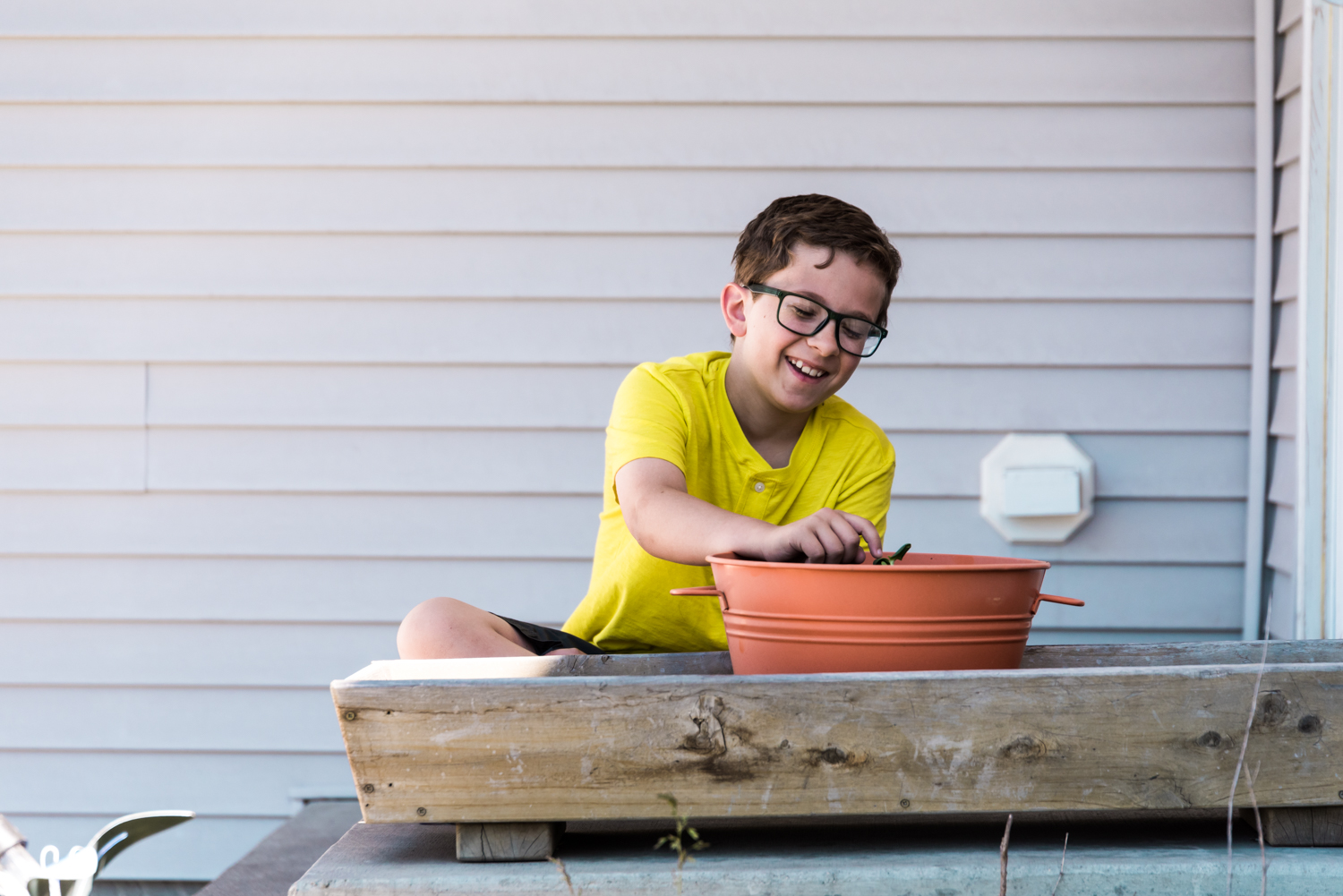 Boy caring for planted seeds in Fargo.