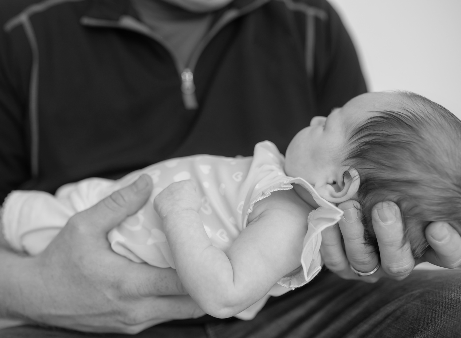 Baby girl being held in her father's hands.