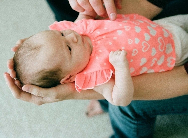 Unposed newborn baby held in her mother's arms.