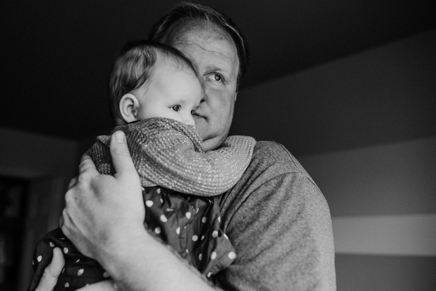 Dad hugging his baby looking out the window.