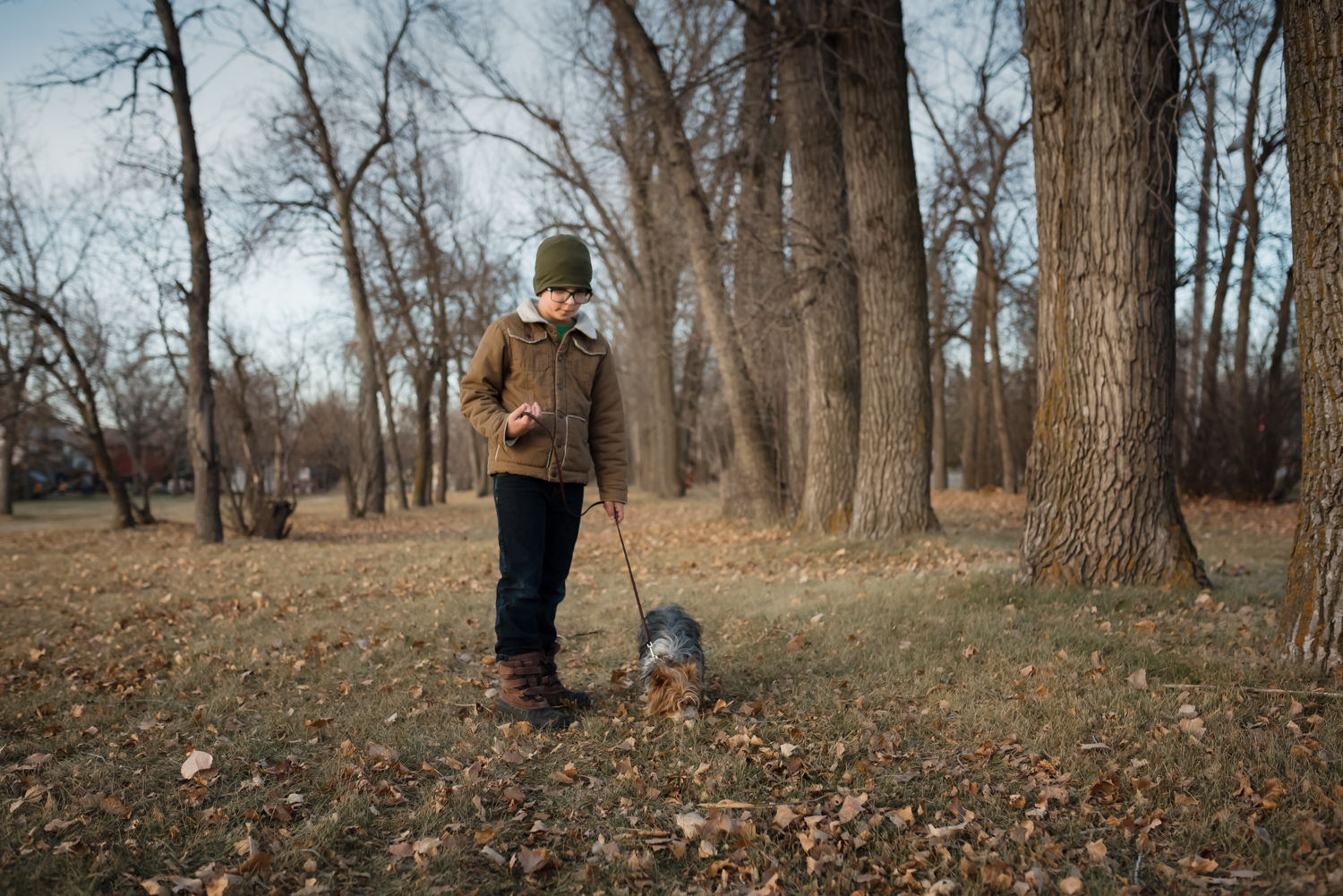 Photo by Mindy Sauvageau (www.orangemoonphotography.com) Boy and his dog walking in a park in West Fargo.