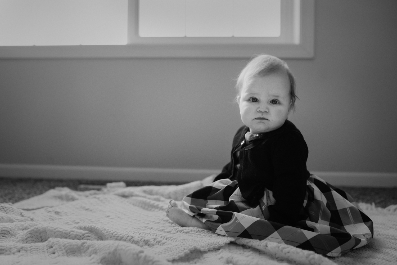 Picture of a six month old baby sitting in her nursery.