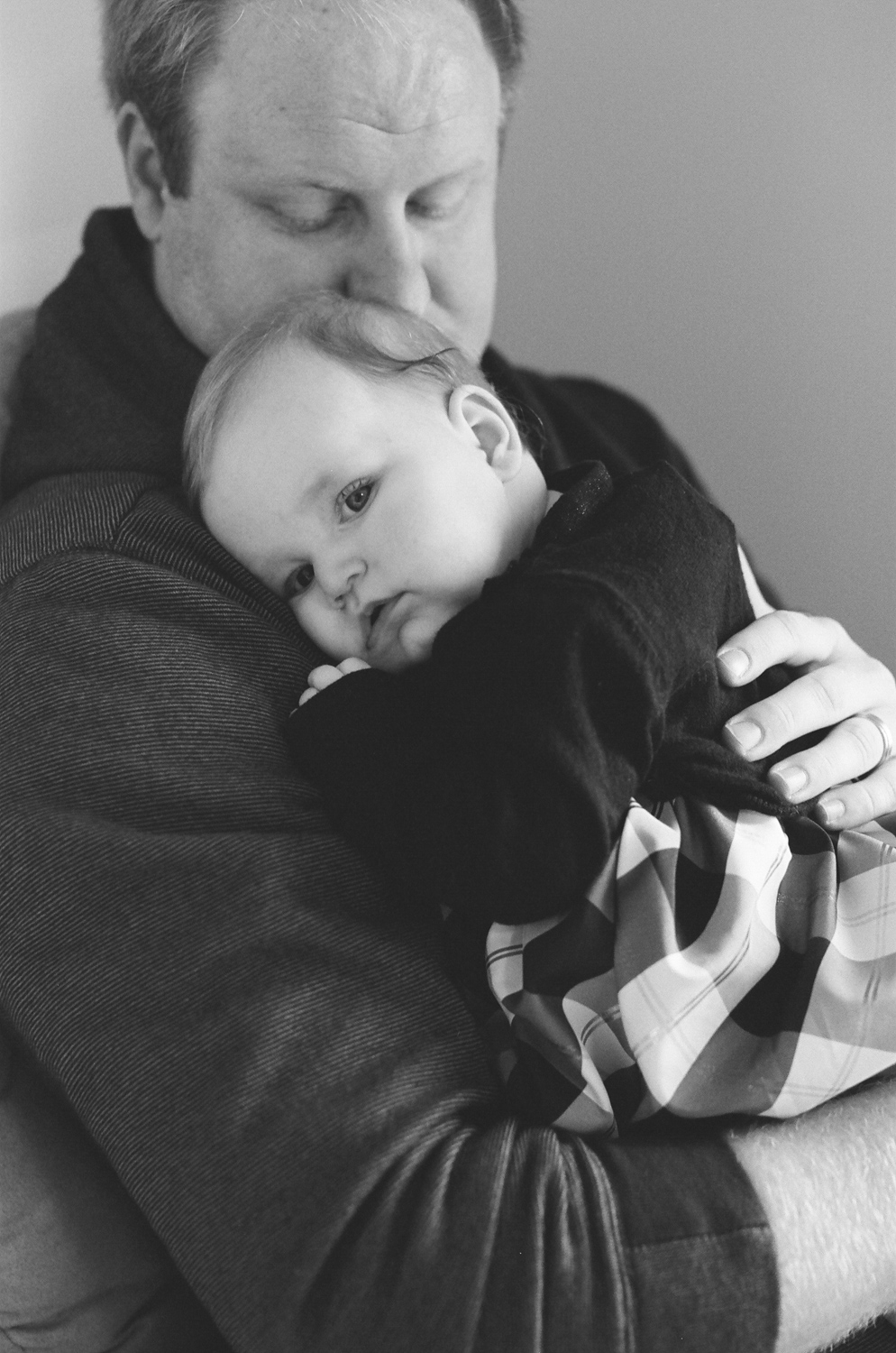 Dad holding his baby girl on his shoulder.