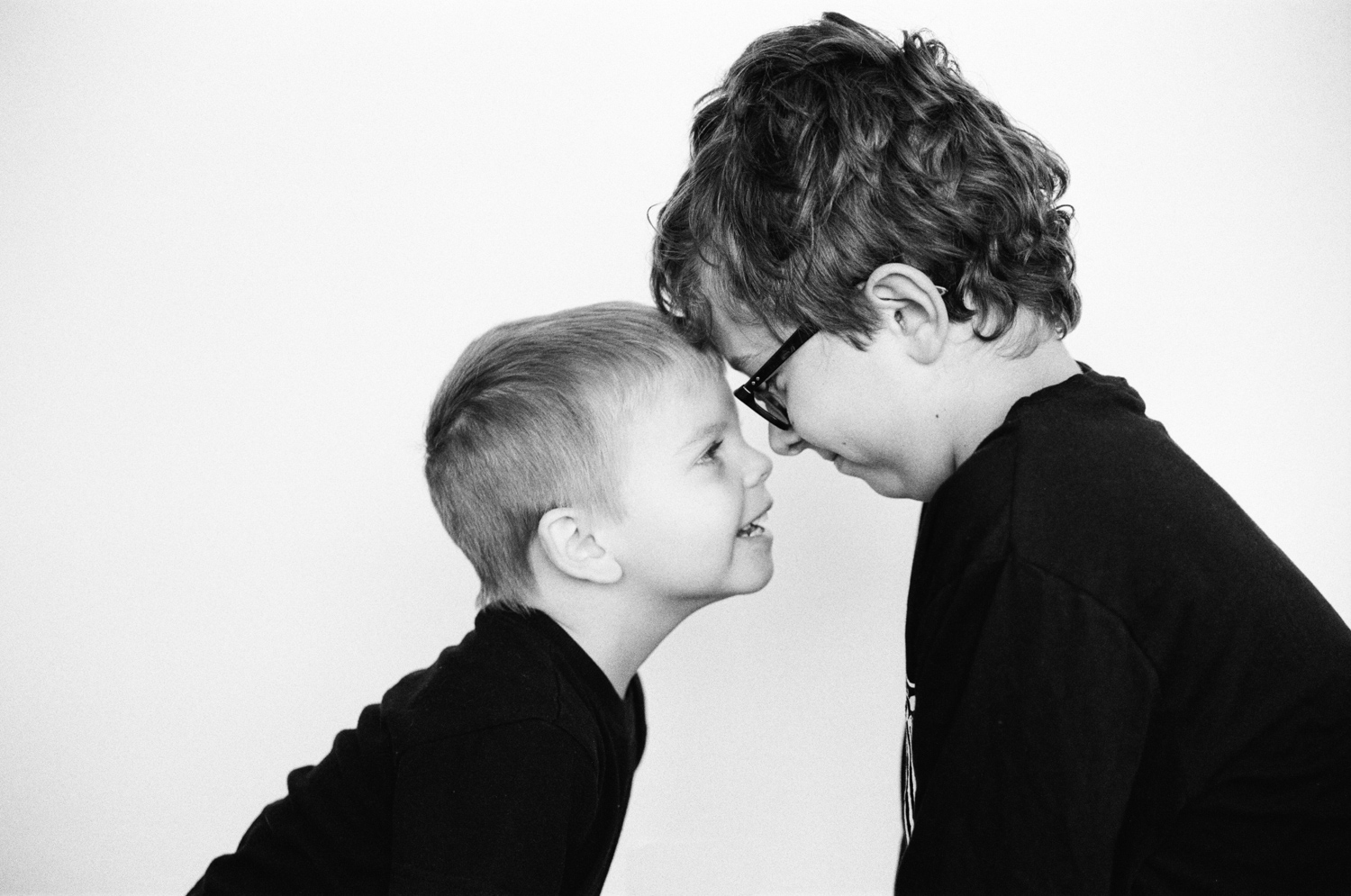 Portrait of two boys touching foreheads smiling