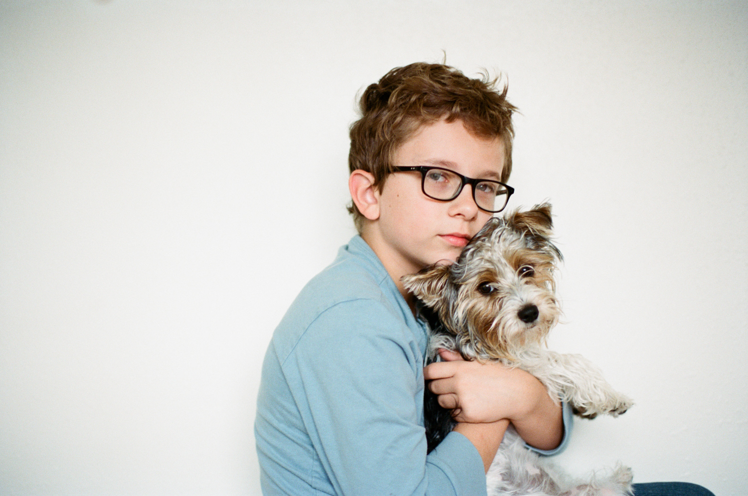 Portrait of a boy hugging his little Yorkshire Terrier dog during a portrait session in Fargo.