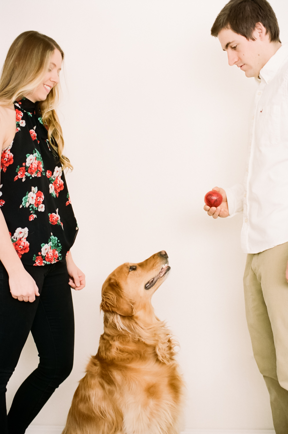 Portrait of a couple playing ball with their golden retriever.