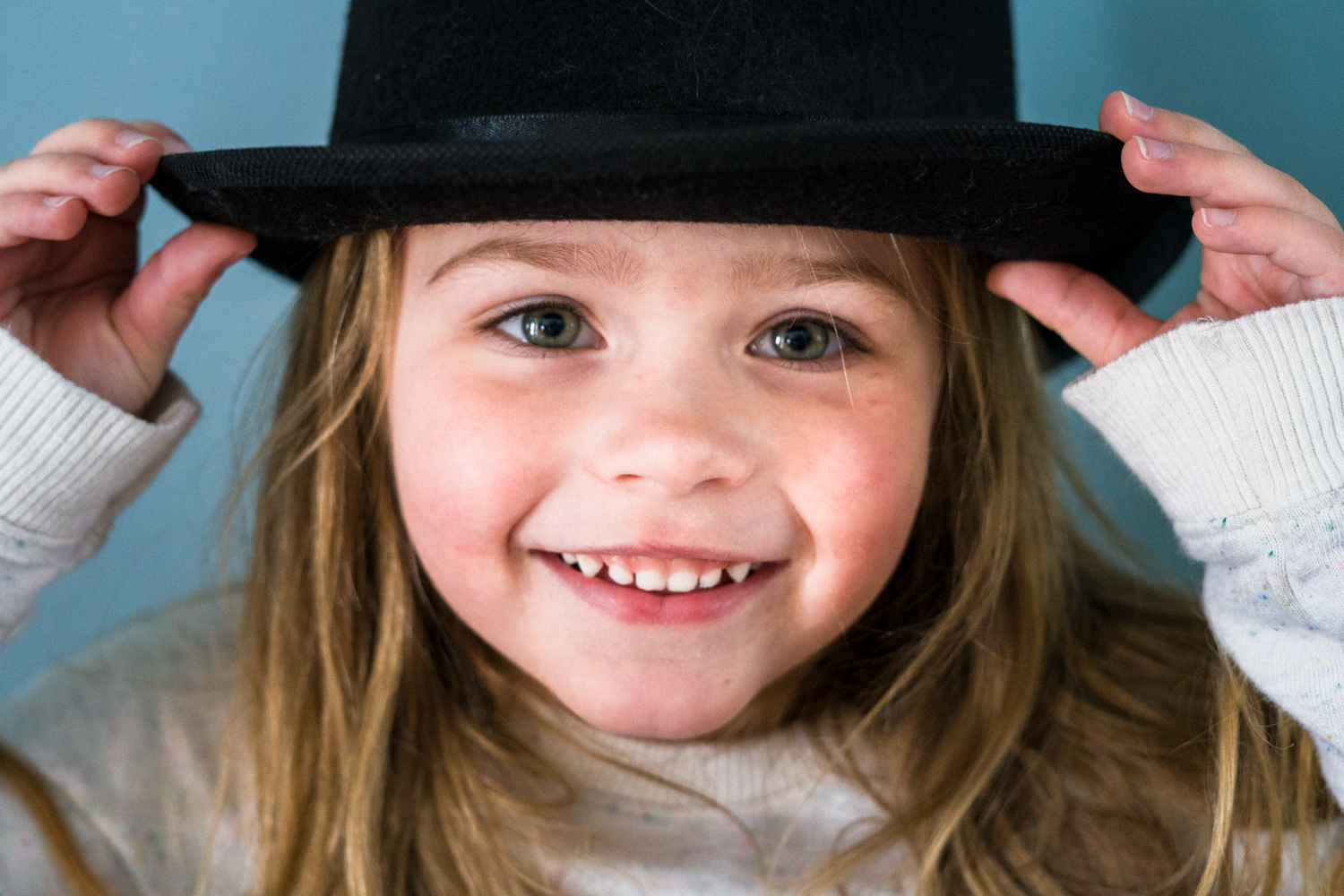Portrait of a girl wearing a hat during dramactic play and smiling at daycare in Fargo.